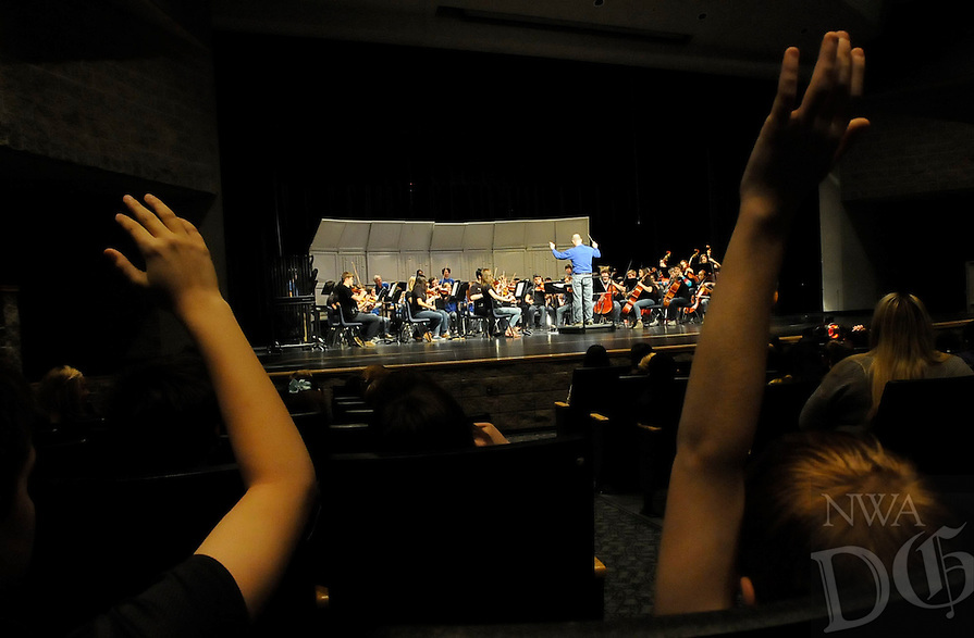 NWA Democrat-Gazette/FLIP PUTTHOFF <br /> Students raise their hands on Tuesday Jan. 27 2015 to indicate they know the tune played by the Rogers High School band and orchestra students.