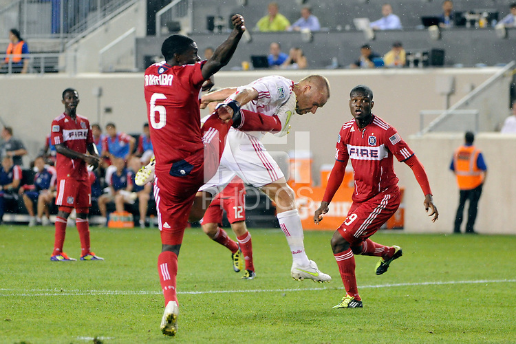 Joel Lindpere (20) of the New York Red Bulls takes a boot to the face from Jalil Anibaba (6) of the Chicago Fire. The New York Red Bulls and the Chicago Fire played to a 2-2 tie during a Major League Soccer (MLS) match at Red Bull Arena in Harrison, NJ, on August 13, 2011.