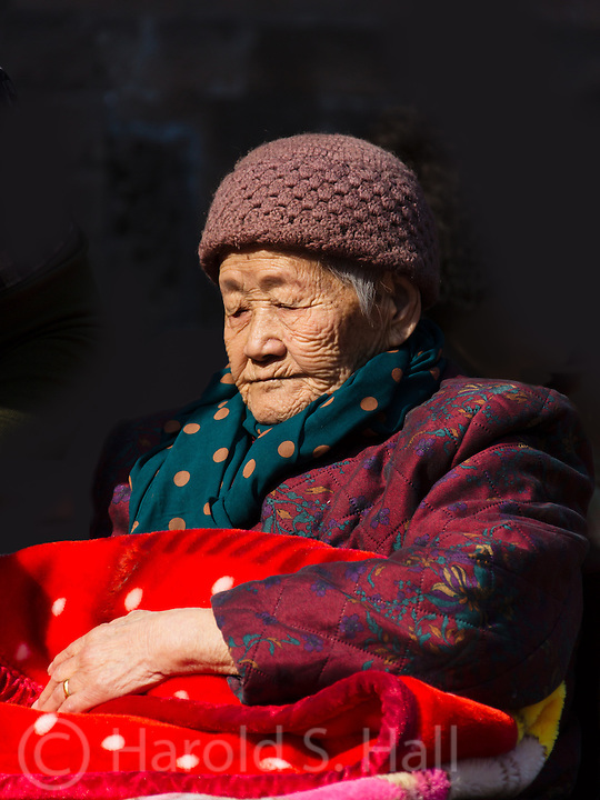 An elder lady visits Tienanmen Square in Beijing, China with her family.