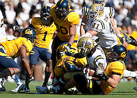 Mike Mohamed brings down Josh Smith with help from J.P. Hurrell. The California Golden Bears defeated the UCLA Bruins 35-7 at Memorial Stadium in Berkeley, California on October 9th, 2010.
