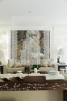 Screening off the living room is Sidana, a painting on transparent acrylic by Saudi artist Basmah Felenban. It hangs above the a classic console table with mother of pearl inlay by Nada Debs.