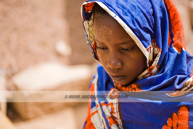 Yuma Dicko, a young Fulani woman in Ouagadougou, Burkina Faso, touches her forehead to the ground for the afternoon prayer.  The Fulani are typically Muslim.  Traditionally pastoralist, they can be found throughout West Africa, crisscrossing the continent in search of water and green pastures for their cattle.