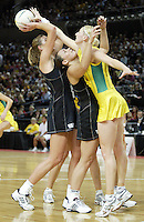 Silver Ferns Irene Van Dyk looks to shot over team mate Jodi Te Huna as Australian Demelza Fellows leans in during the netball test match between the Silver Ferns v Australia played at the Sydney Superdome, Sydney Australia, 29th June 2005. The Silver Ferns won 50-43. ©Michael Bradley