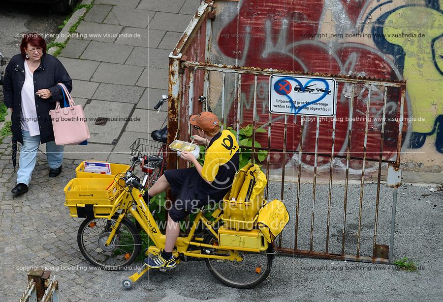 GERMANY , Hamburg, German Mail, short break of the postman, lunch time on bicycle /DEUTSCHLAND, Hamburg, Deutsche Post, kurze Mittagessen des Postboten auf dem Fahrrad