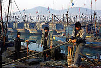 A fisherman on a fishing boat in a harbour at Chuwang fishing village. It is 250 km from Beijing. The Chinese fishing industry is in decline with the government cut of 10% of boats, which amounts to 10,000 boats and 30,000 fishermen. Most boats in Chuwang have not been put to sea for two weeks. Penglai, China.<br /> 26-JAN-02