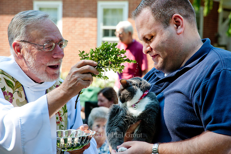 "Photo by Phil Grout..Father Sam Edleman, assistant priest of Ascension Church, Westminster, uses a hyssop branch.to sprinkle holy water on ""Bazooka"", held by Kevin McIntyre of Westminster during a special.""blessing of the animals"" outdoor service at the church.  McIntyre organized the.service which brought many four-legged friends from throughout the parish to receive.the blessings of the church.."