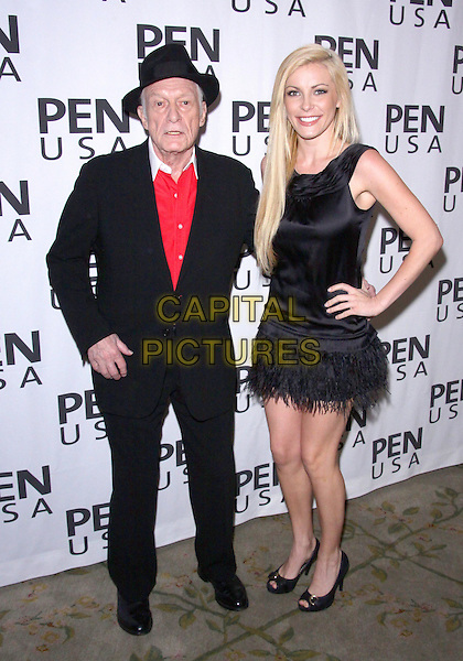 HUGH M. HEFNER & CRYSTAL HARRIS .20TH Annual Literary Awards Festival held at the Beverly Hills Hotel, Beverly Hills, CA, USA, .17th November 2010..full length suit jumper sweater dress sleeveless feathers feather hand on hip black hat red white  peep toe shoes couple .CAP/ADM/TC.©T. Conrad/AdMedia/Capital Pictures.