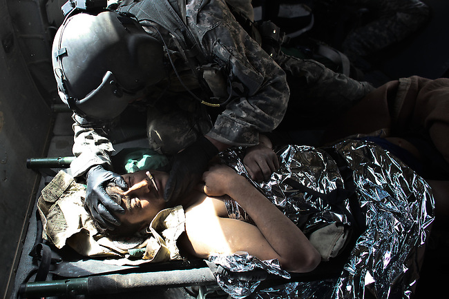"Sgt. Patrick Schultz, 31, a flight medic with the 101st Combat Aviation Brigade's ""Shadow Dustoff""  treats an Afghan soldier wounded in a Taliban ambush south of Kandahar, Afghanistan. Sept. 21, 2010. DREW BROWN/STARS AND STRIPES"