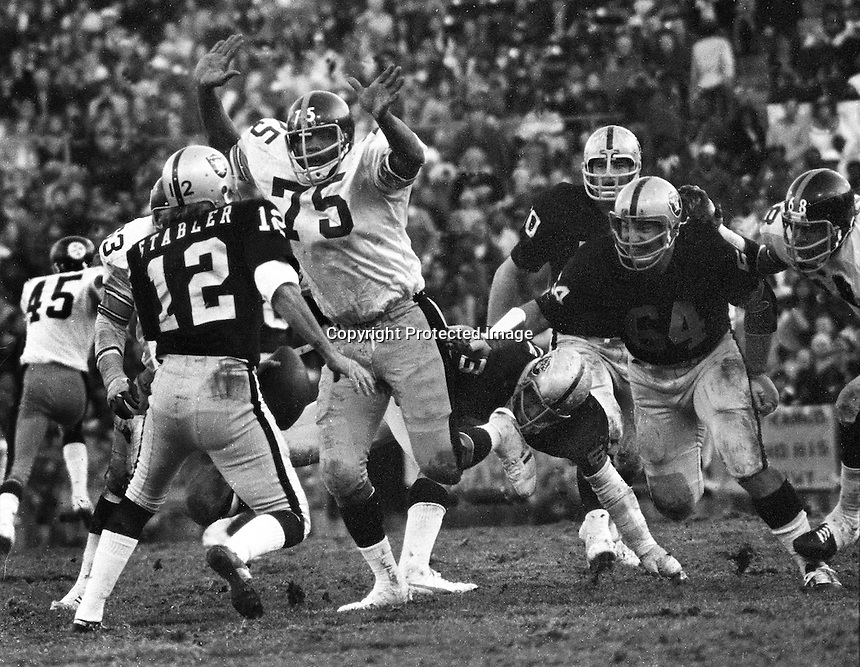 "Oakland Raider quarterback Ken Stabler is about to be sacked by ""mean"" Joe Green of the Pittsburg Steelers.(1974 photo by Ron Riesterer)"