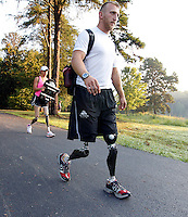 Former Marine sergeant Rob Jones, right, walks with partner Oksana Masters on their way to the boat dock to train Wednesday July, 25, 2012 on the Rivanna River in Charlottesville, VA. Former Marine sergeant Jones, who lost both legs during an IED explosion in Afghanistan, will compete with Masters as rowers at the 2012 Paralympics in London, England. Rowing will make its appearance at the London Paralympic Games for only the second time, after its introduction at the Beijing 2008 Games.