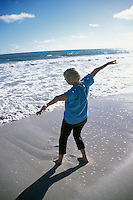 USA, Hawaii, Oahu, Kailua Beach, mature woman on beach celebrating sunrise.