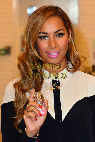 Leona Lewis at The Body Shop launch.  Singer and animal rights campaigner appears in store to launch her own line of make up featuring lip glosses, blusher palettes and a face make-up brush, as part of the iconic store's Cruelty Free Beauty campaign. The Body Shop, Westfield London Shopping Centre, White City, London, England..March 27th, 2013.headshot portrait black white pink lipstick hand bottle red nail varnish polish shirt .CAP/BF.©Bob Fidgeon/Capital Pictures.