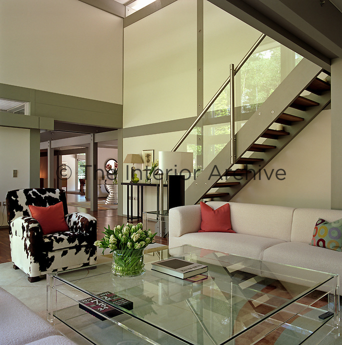 The sofa is tucked under the staircase that leads up to the mezzanine library and faces a large perspex coffee table