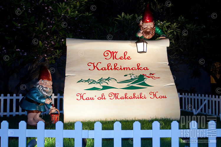 "Friendly wooden elves accompany a sign proclaiming ""Mele Kalikimaka"" (""Merry Christmas"") and ""Hau'oli Makahiki Hou"" (or ""Happy New Year"") during the holiday season in downtown Honolulu, O'ahu."