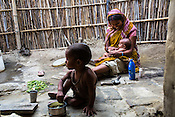 Maina Devi plays with her 3 month old daughter, Priya while her son, Pradeep (2) eats his breakfast in the courtyard of their hut in Bhelaiya village in Raxaul, Bihar, India.