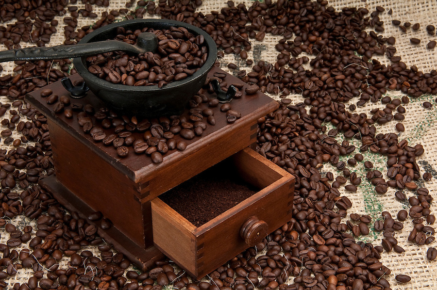 Old coffee grinder and coffe beans over burlap.
