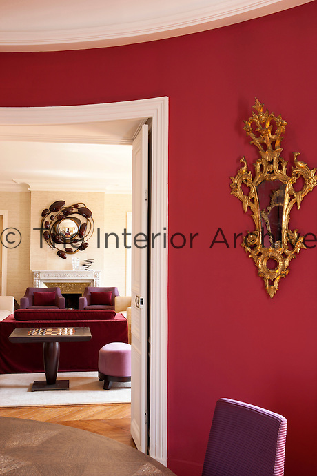 The curved red-painted walls of the dining room reflect the colour of the soft furnishings in the adjacent living room