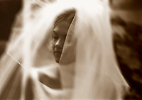 A bride is surrounded by her veil as she prepares for her wedding ceremony. (Photo by Scott Eklund/Red Box Pictures)