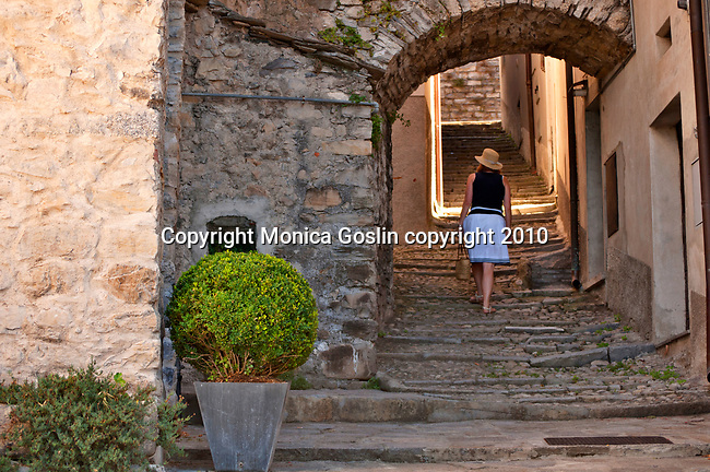 A woman wearing a straw hat walks up a cobble stone, arched path in Sala Comacina, a town on Lake Como, Italy