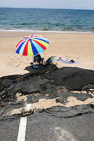 Tony Cannata (under umbrella) and Linda Cannata, of Mashpee, Mass., sit on the beach with their dogs near a portion of collapsed parking lot at Herring Cove Beach in the Cape Cod National Seashore outside of Provincetown, Mass., USA, on Fri., July 1, 2016. Portions of the parking lot have been closed after land eroded during storms earlier this year. Linda says she grew up on the Cape and the two of them come to beach nearly every weekend during the summer.