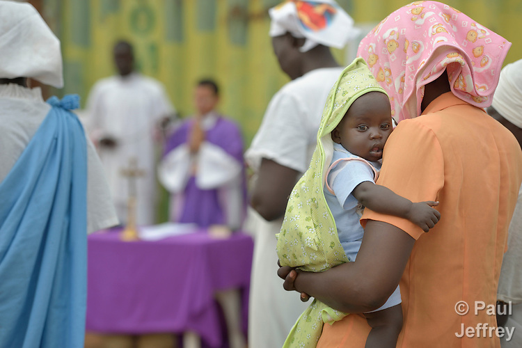 A mother holds her child during Catholic Mass held in a camp for internally displaced families located inside a United Nations base in Juba, South Sudan. The camp holds Nuer families who took refuge there in December 2013 after a political dispute within the country's ruling party quickly fractured the young nation along ethnic and tribal lines. More than 20,000 people are living in the camp.