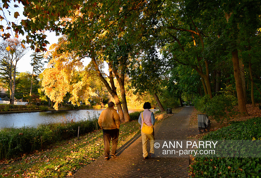 Port Washington, New York, U.S. 27th October 27, 2013. A man and woman walk on a path with fall foliage along a pond at a North Shore park on Long Island at dusk.