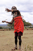 Lolgorian, Kenya. Young Moran Siria Maasai with colourful bead necklaces, showing how he killed a lion.