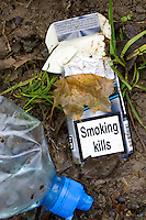 Cigarette packet showing SMOKING KILLS and plastic bottle discarded by road, Oxfordshire, UK