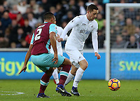 Gylifi Sigurdsson of Swansea City FC looks for a way past Winston Reid of West Ham United during the Premier League match between Swansea City and West Ham United at The Liberty Stadium, Swansea, Wales, UK. 26 December 2016