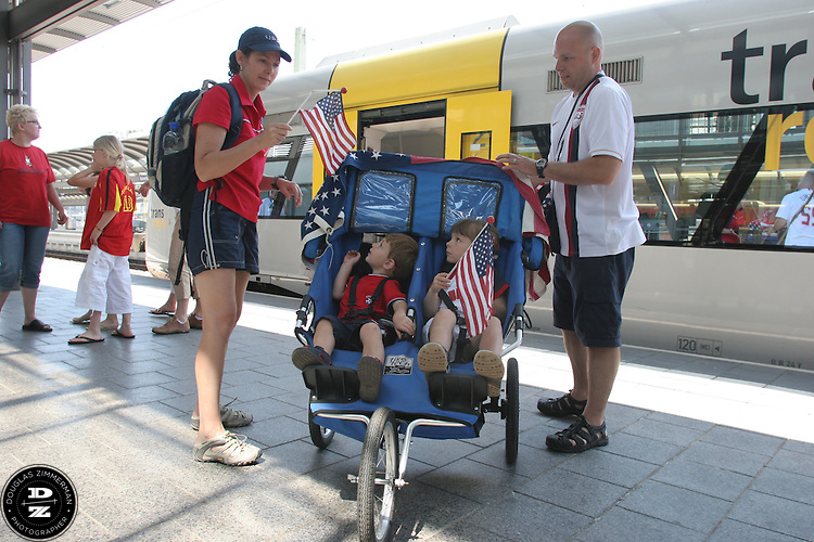 USA National Soccer Team fans Zackary Zaman 2 1/2 years old, and Dezirae Zaman, 4 1/2 years old,  are handed a flag from their mother Lynn  while their father Jeff gets ready to push them from the Kaiserslautern train station.  They arrived early before their FIFA World Cup First round match against Italy on Saturday June 17th, 2006 in Kaiserslautern, Germany.  The USA and Italy tied 1-1.