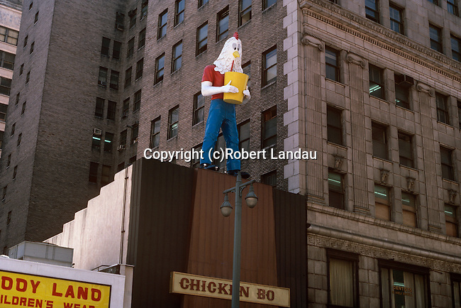 Legendary Chicken Boy figure perched on a roof in a downtown Los Angeles, 1982