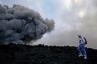 Tourist walking near the smoke billowing from the crater of Yasur Volcano, Tanna Island, Vanuatu.