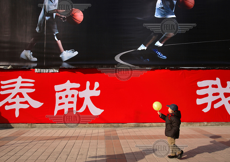 A child walks with a balloon beside a 2008 Olympic Games poster featuring young basketball players.
