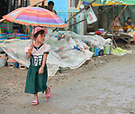A girl walks through the Tahan Market in Kalay, a town in Myanmar. This market is located in Tahan, the largely ethnic Chin section of the town. The girl has thanaka, a cosmetic paste, on her face.