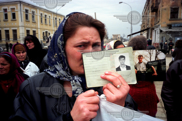 ©ÊHeidi Bradner / Panos Pictures..Grozny, Chechnya. Russia...A Chechen woman shows the passports of her missing sons, during a gathering of women searching for arrested and missing male relatives. Their protest was timed to coincide with International Women's Day, a Soviet-era holiday to honour women of the USSR.