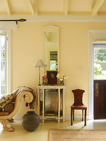 The living room is decorated in neutral tones. A mirror hangs above a glass display cabinet; an Empire style sofa stands to one side.