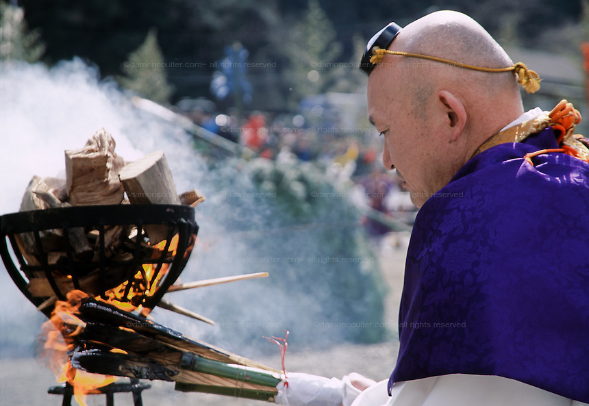 A Yamabushi or Mountain priest in purple robes lights a wooden torch which will later be used to lite a large fire of cedar branches during the Hi Watari fire walking festival in Takao san Guchi, near Tokyo Japan. Sunday March 11th 2007