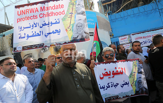 Palestinian students hold placards during a rally in support of the headquarters United Nations Relief and Works Agency (UNRWA), outside its headquarters in Gaza City on September 17, 2019. The US decided to cut 300 million US dollars of its funding to UNRWA last year, followed by a further 60 million US dollars in January this year, which is expected to affect services provided to nearly five million Palestinian refugees located in Syria, Jordan, Lebanon, the Gaza Strip, West Bank, and East Jerusalem. Photo by Ashraf Amra