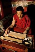 A monk at the Sera Monastery in Lhasa studies Buddhist scriptures (sutra), while collecting the small twenty Yuan fee tourists are charged to take pictures.