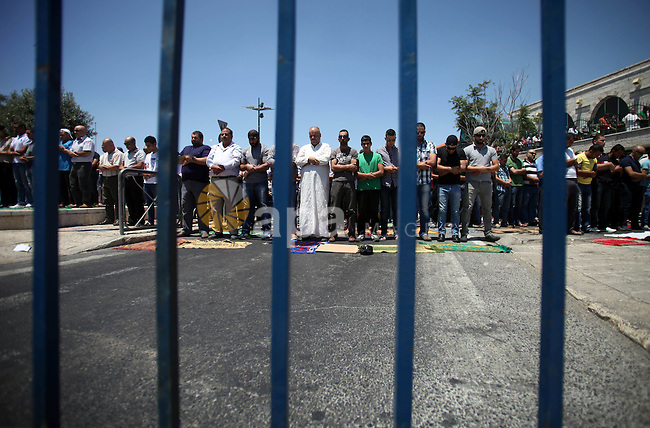 Palestinian muslim worshipers pray on the third Friday of the holy month of Ramadan as Israeli police (not seen) stand guard in the Arab east Jerusalem neighbourhood of Ras al-Amud July 18, 2014. An Israeli police spokesman said on Friday that police allowed only Palestinian men over the age of 50 to enter a compound and added that seven people were detained on suspicion of throwing stones at police officers after the prayers on the compound. Photo by Saeed Qaq