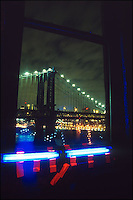 A night view of Manhattan Bridge through a dark window with black lights and red ribbons.