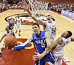 Duke's Austin Rivers (0) drives to the bucket between FSU's Jon Kreft (50) and Xavier Gibson (1).  The 15th ranked Florida State Seminoles fell to the 4th ranked Duke Blue Devils 74-66 in their NCAA basketball game in Tallahassee, Florida November 23, 2010.