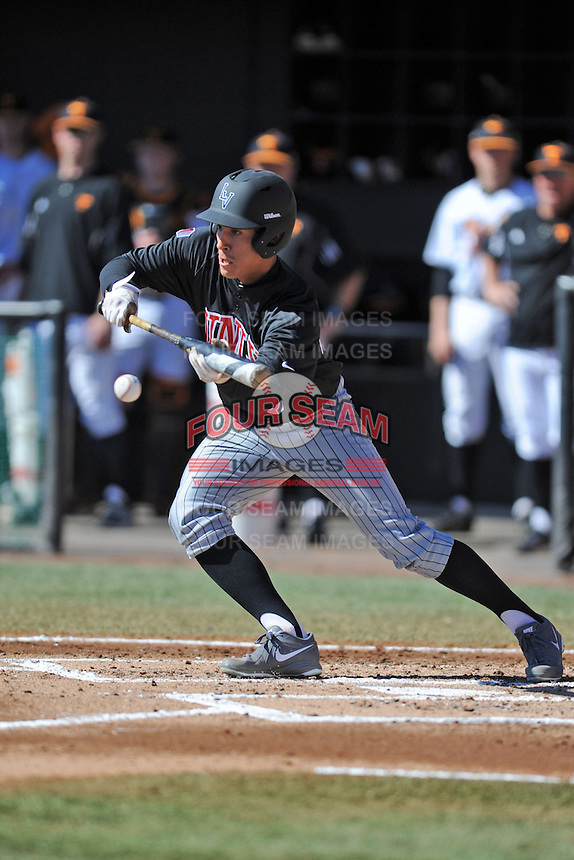 UNLV Runnin' Rebels left fielder Johnathan Torres #33 attempts a bunt during a game against the Tennessee Volunteers at Lindsey Nelson Stadium on February 22, 2014 in Knoxville, Tennessee. The Volunteers defeated the Rebels 5-4. (Tony Farlow/Four Seam Images)