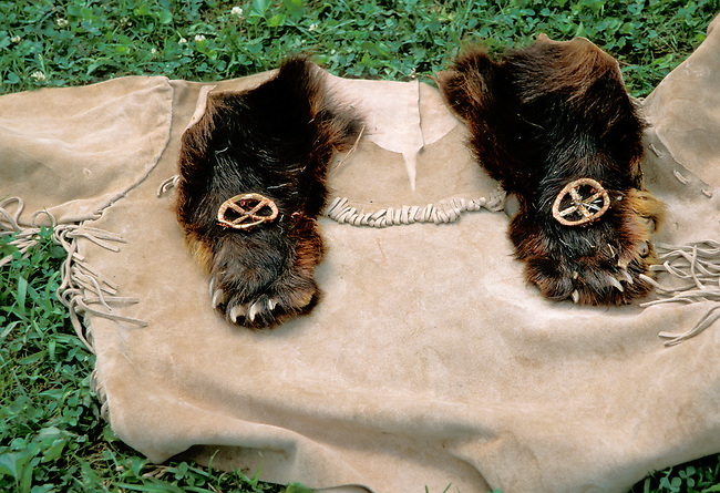 A pair of bear fur moccasins made from the actual feet along with the bears claws laid out for display on a buckskin shirt with fringe