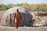 Fulani man in the seasonal village of Bantagiri in northern Burkina Faso.  The Fulani are traditionally nomadic pastoralists, crisscrossing the Sahel season after season in search of fresh water and green pastures for their cattle and other livestock.  The straw mat house can be reassembled and dissasembled at will.