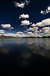 White clouds on a blue sky over a lake