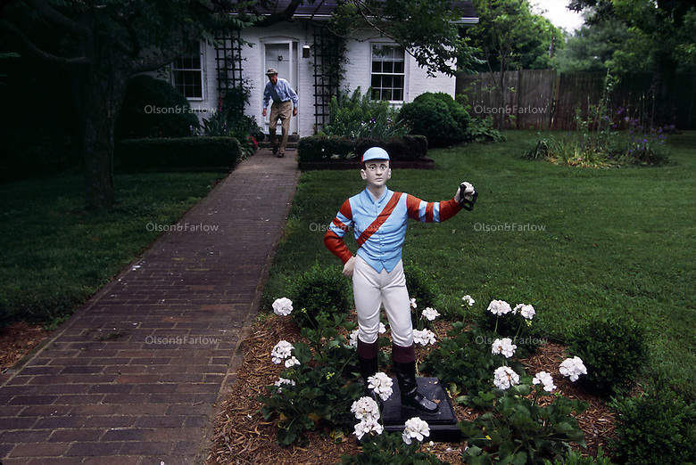 The Bluegrass Region is rich with lore and traditions--the lawn jockey, small statue is prominently positioned on every farm with a lantern or hitching ring in one outstretched hand.   Legend traces back to when Jocko Graves stood guard over horses for George Washington and froze to death holding a lantern in his hand. He was known as the faithful guardsman. <br /> <br /> Modern day watchman and farm owner Dr.Smiser West walks out his office door toward the lawn jockey painted in the colors of Waterford Farm.