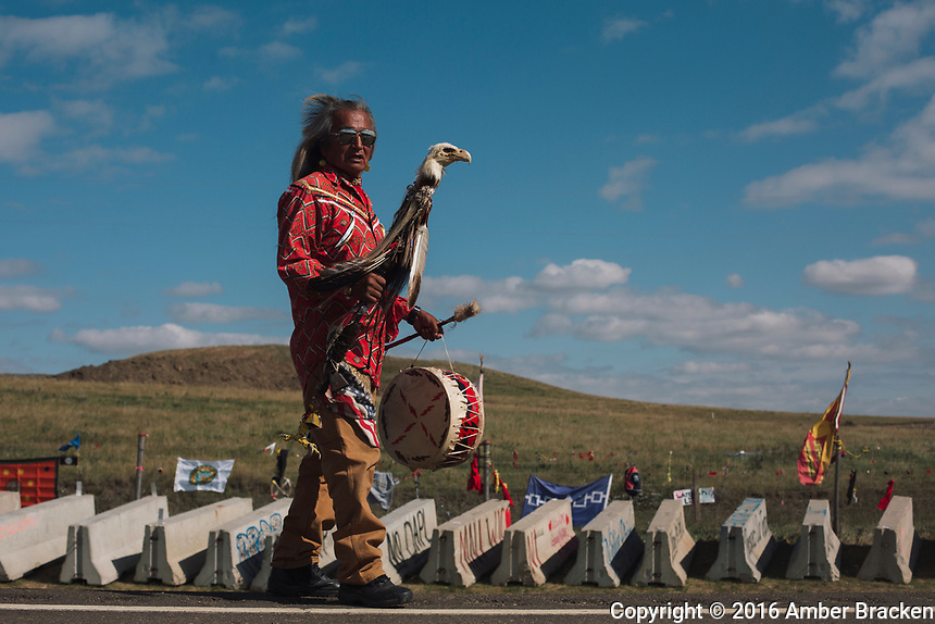 """Staff carrier Phil Littlethunder, Lakota from Rosebud, SD, on the highway outside a pipeline construction site north of Sacred Stone Camp, ND on Tuesday, September 13, 2016.  The staff was passed to him by his uncle, Bill Littlethunder, when he taught the younger man to dance. Phil's uncle told him never to dance for money and, even though many people say he should, he still won't. """"I dance for the people, I dance for the healing, I dance for the ancestors. I dance for those who can't dance."""""""