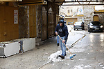 A Palestinian man removes snow during a winter storm, in the West Bank city of Hebron, on January 17, 2019. Photo by Wisam Hashlamoun