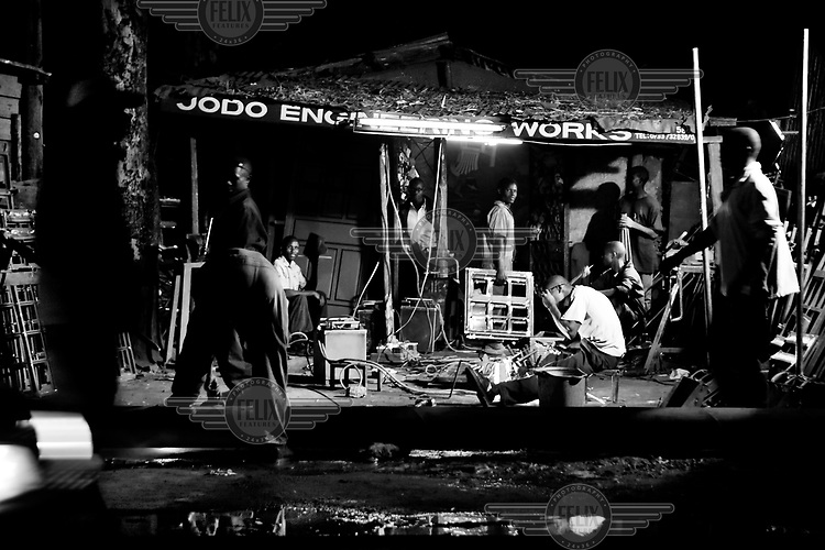 Young men work the night shift in a car repair shop. Most shops in Kibera stay open until midnight.